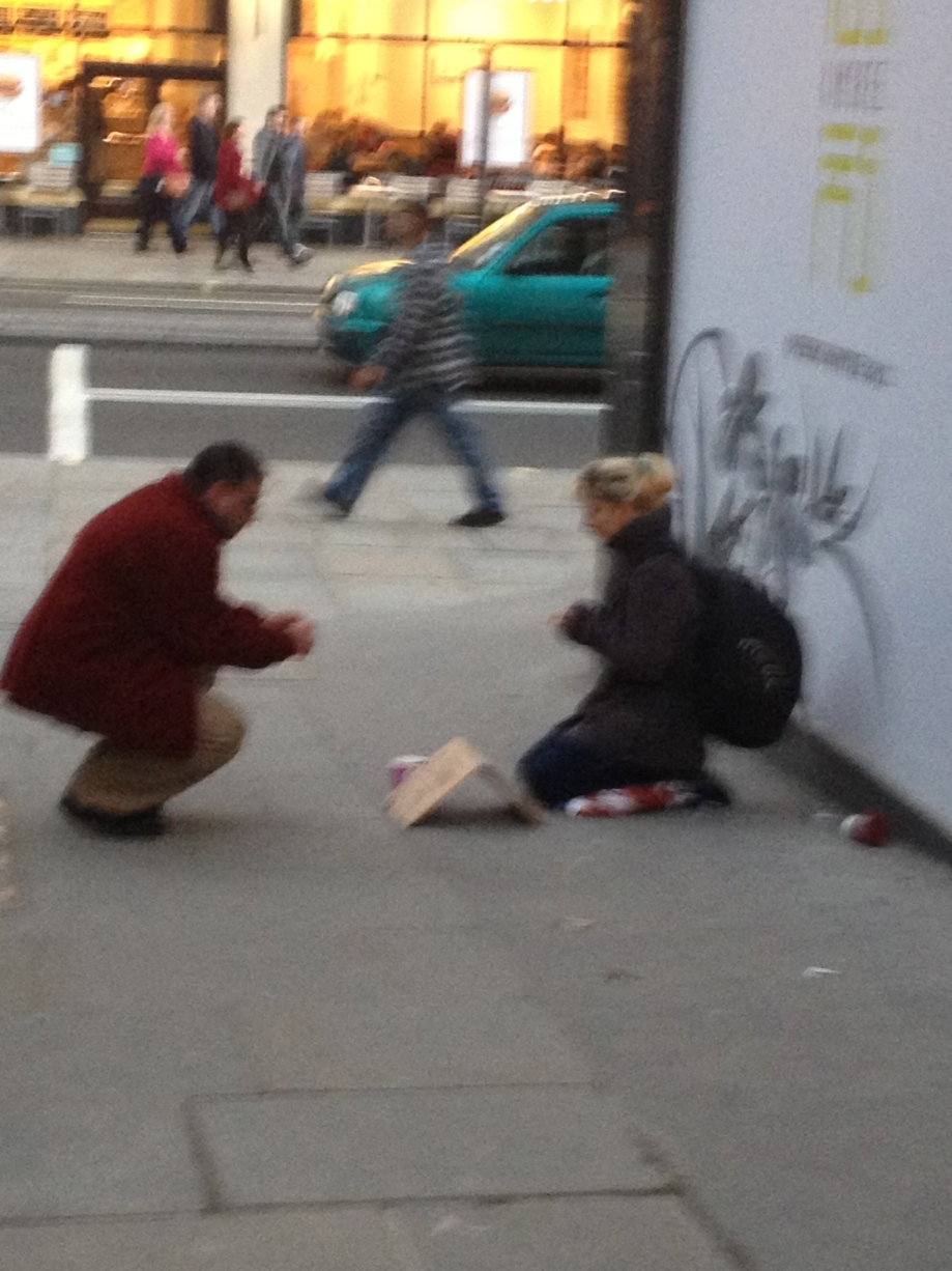 Guy taking a picture of homeless sign